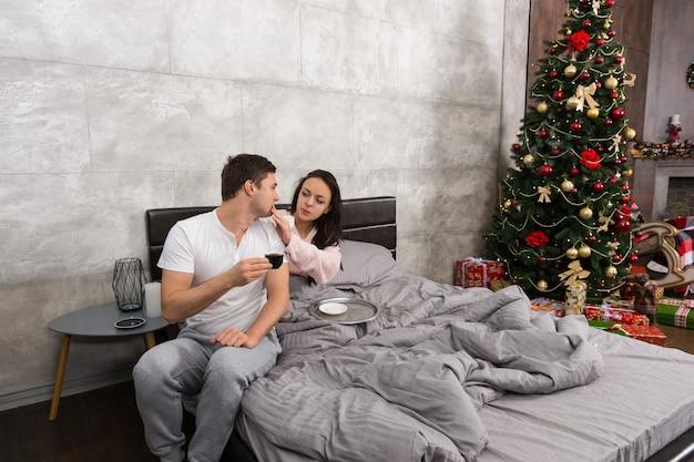 젊은 여성은 침대에서 커피를 마시고 잠옷을 입고 크리스마스 트리와 선물이 있는 침실에서 남편을 돌봅니다.