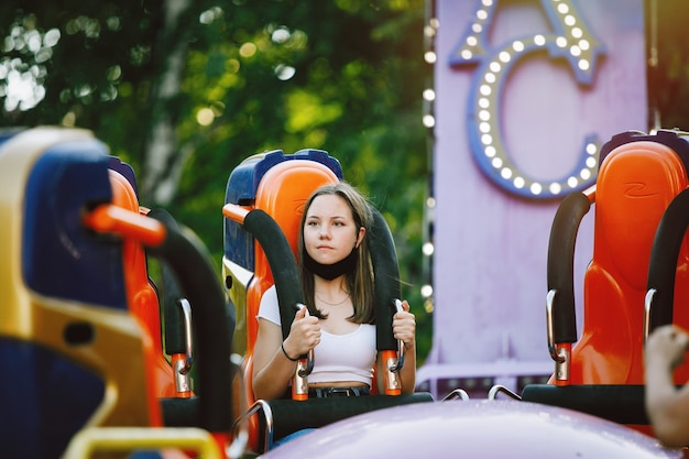 Young woman on carousel or attraction in summer amusement park in the city