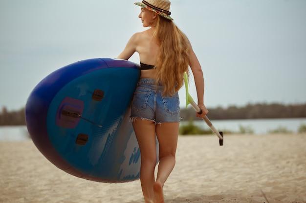 La giovane donna porta il paddle board in spiaggia
