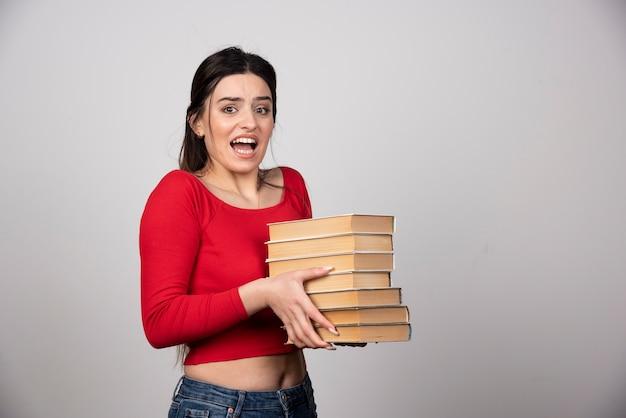 たくさんの本を運ぶ若い女性