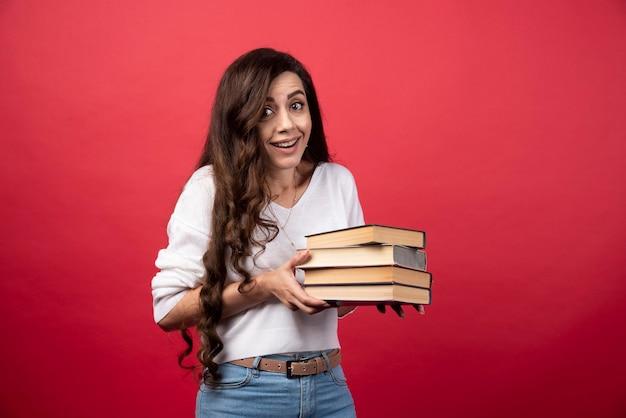 빨간색 배경에 책을 들고 젊은 여자. 고품질 사진