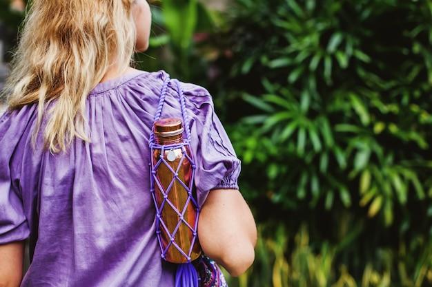 再利用可能なnoplastic銅の水ボトルを運ぶ若い女性