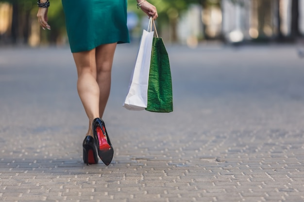 Of young woman carrying shopping bags while walking along the street. woman sexy legs with handbag.