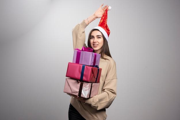 クリスマスプレゼントの3つの箱を運ぶ若い女性。 無料写真