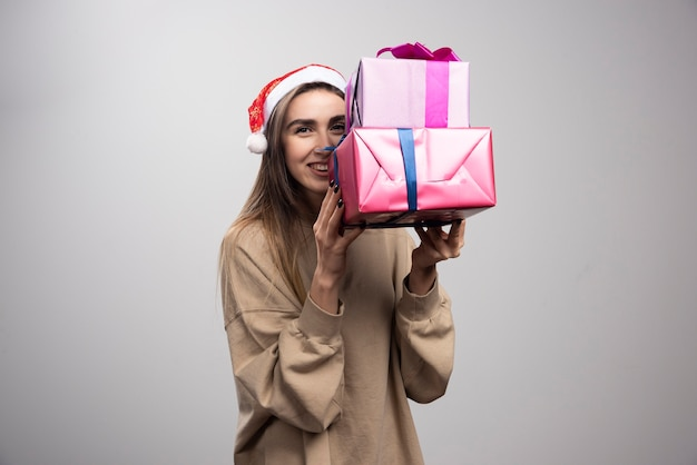 Young woman carrying two boxes of christmas presents.