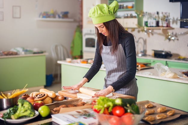 Young woman in casual clothes, apron and hat rolling dough for a pie in kitchen. female baker making pastry