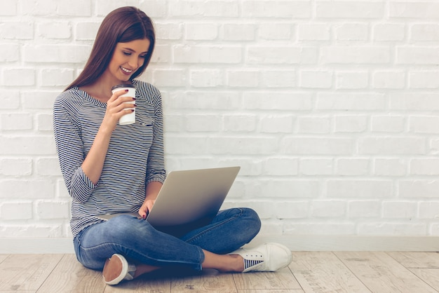 Young woman in casual clothes is using a laptop.