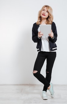 Young woman in casual clothes thinking and holding tablet computer