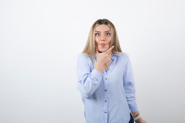 Giovane donna in abito casual che guarda l'obbiettivo sul muro bianco