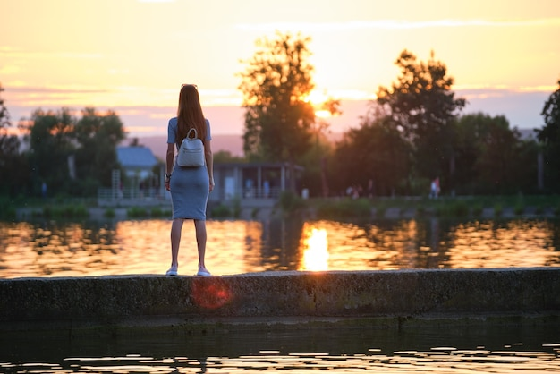 Young woman in casual outfit relaxing on lake side on warm evening. summer vacations and travelling concept.