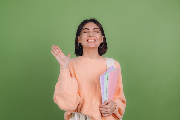 Young woman in casual peach sweater and backpack isolated on green olive color wall