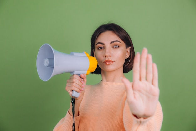 Young woman in casual peach sweater isolated on green olive color wall. unhappy serious with megaphone doing stop sing with palm of the hand