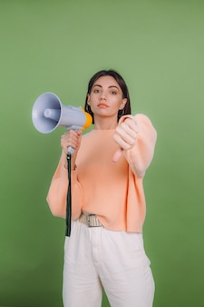 Young woman in casual peach sweater isolated on green olive color wall