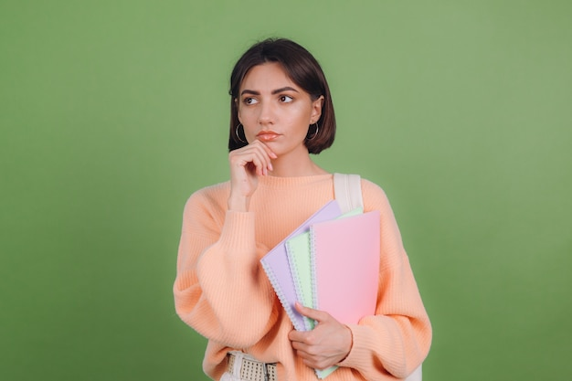 Young woman in casual peach sweater isolated on green olive color wall Premium Photo