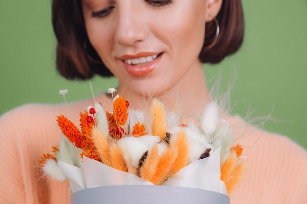 Giovane donna in maglione pesca casual isolato sul muro verde oliva tenere arancione fioriera bianca composizione di fiori di cotone gypsophila grano e lagurus per un regalo felice stupito sorpreso