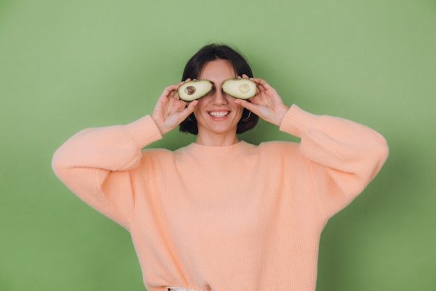 Young woman in casual peach sweater isolated on green olive wall holding  avocado, health and skin care concept, copy space