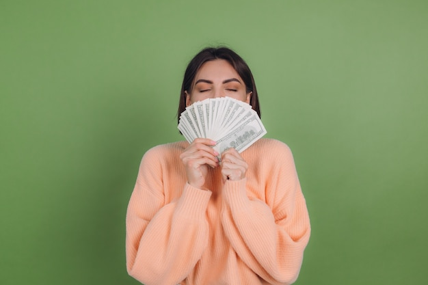 Young woman in casual peach sweater isolated on green olive wall