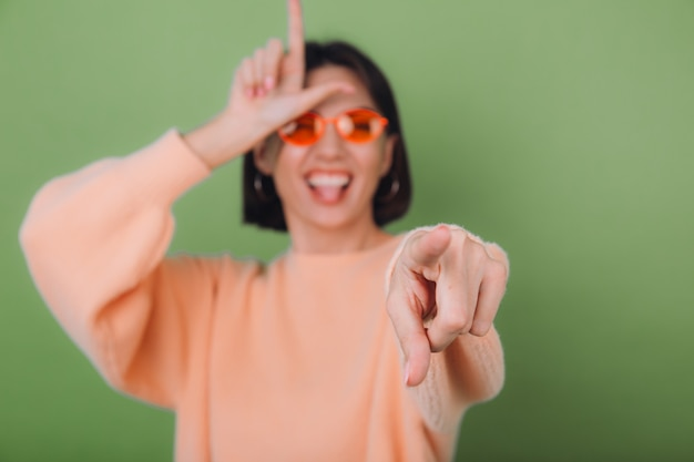 Young woman in casual peach sweater and orange glasses isolated on green olive wall pointing at you mockery fool day showing horn symbol copy space