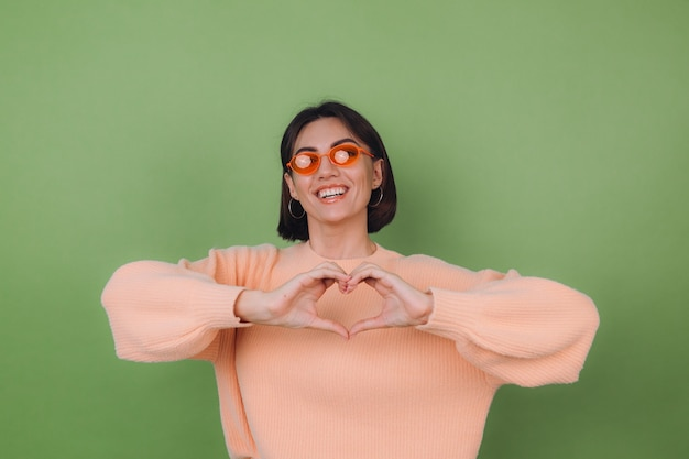 Young woman in casual peach sweater and orange glasses isolated on green olive wall   shows heart with hands love concept copy space