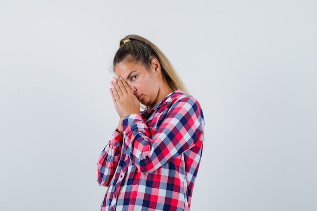 Giovane donna in camicia casual mantenendo le mani nel gesto di preghiera e guardando speranzoso, vista frontale.