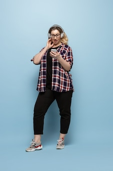 Young woman in casual wear with smartphone and headphones on blue wall. body positive character, feminism, loving herself, beauty concept. plus size beautiful businesswoman. inclusion, diversity.