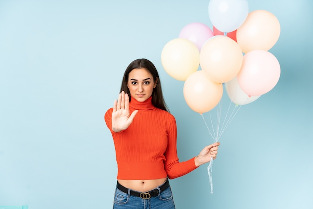 Young woman catching many balloons isolated on blue wall making stop gesture with her hand