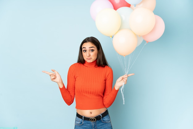 Young woman catching many balloons isolated on blue wall pointing to the laterals having doubts