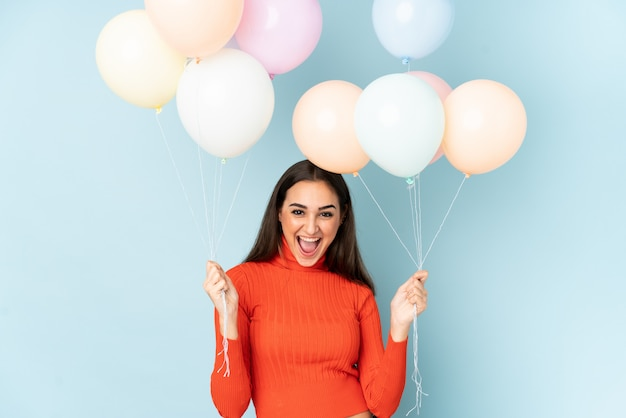 Young woman catching many balloons isolated on blue
