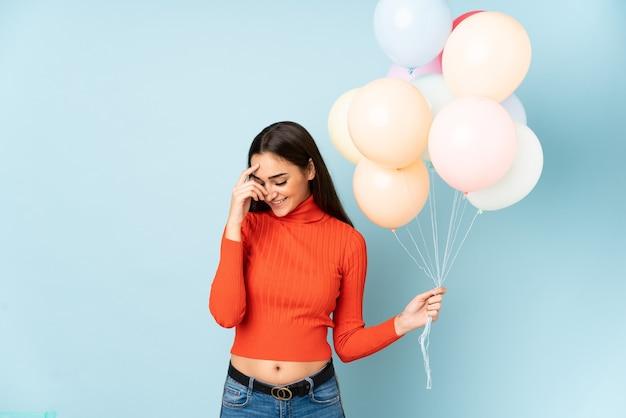 Молодая женщина ловит много воздушных шаров изолированы
