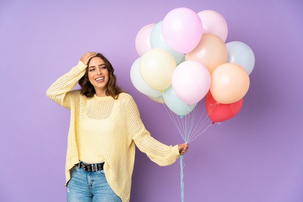 Young woman catching many balloons   on   laughing