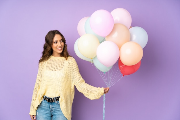 Young woman catching many balloons   on   looking to the side