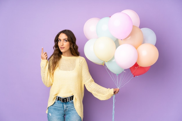 Young woman catching many balloons   on   pointing with the index finger a great idea