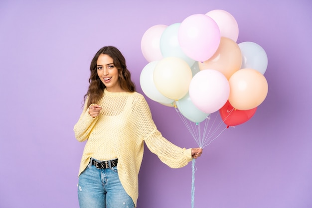 Young woman catching many balloons   on   points finger at you