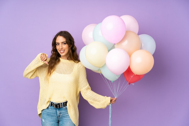 Young woman catching many balloons   on   proud and self-satisfied