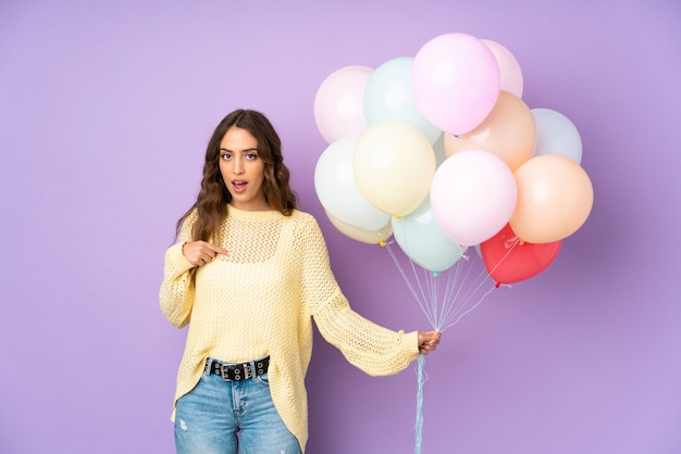 Young woman catching many balloons over on purple wall with surprised facial expression