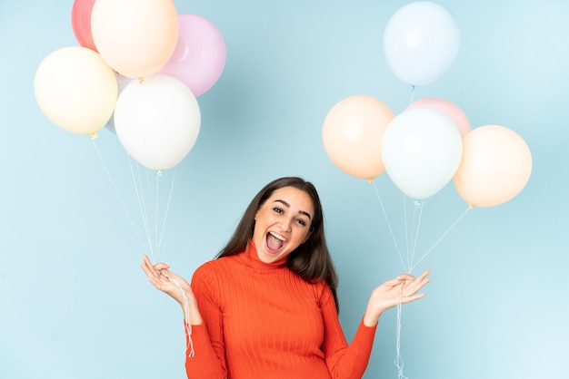 Молодая женщина ловит много воздушных шаров