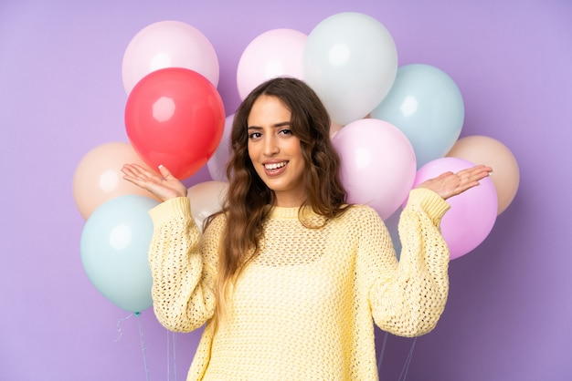 Young woman catching many balloons   on