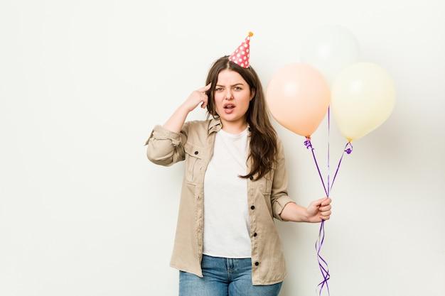 집게 손가락으로 실망 제스처를 보여주는 생일을 축 하하는 젊은 여자.