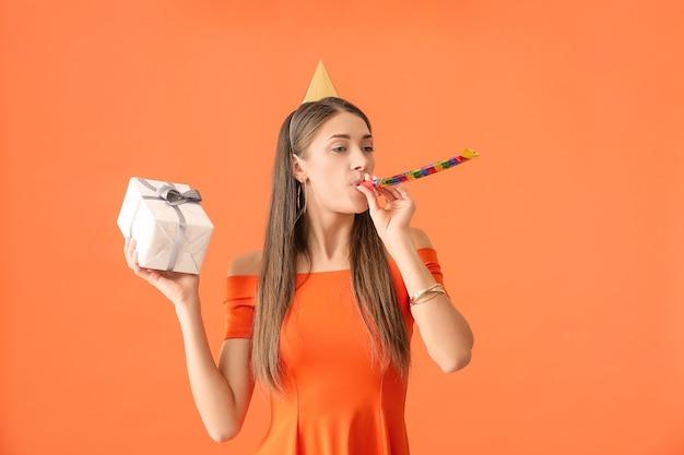 色の背景で誕生日を祝う若い女性