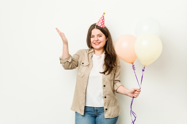 Young woman celebrating a birthday receiving a pleasant surprise, excited and raising hands.
