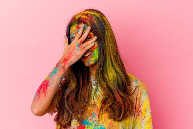 白い壁に隔離された聖なる祭りを祝う若い女性が指でカメラを点滅し、恥ずかしい顔を覆っている