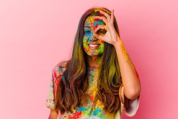 白い壁に隔離された聖なる祭りを祝う若い女性は、目で大丈夫なジェスチャーを維持して興奮している