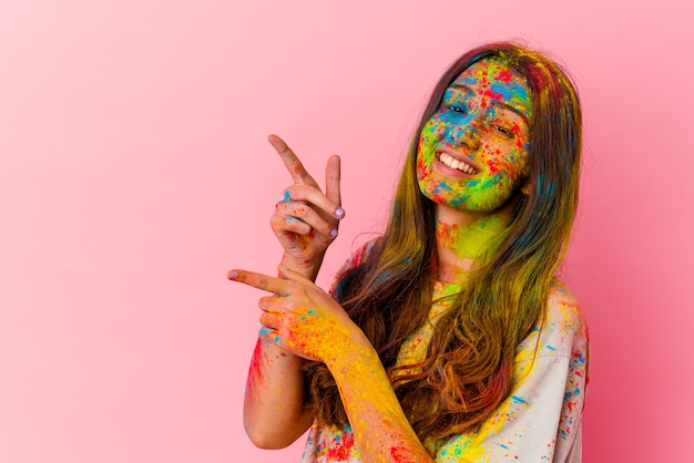 白い壁に隔離された聖なる祭りを祝う若い女性は、人差し指を離れて指差して興奮