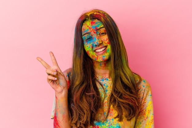 白い壁に隔離された聖なる祭りを祝う若い女性は、指で平和のシンボルを喜んで気楽に示しています