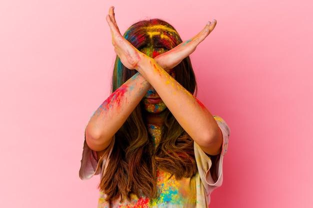 両腕を組んで白い壁に隔離された聖なる祭りを祝う若い女性