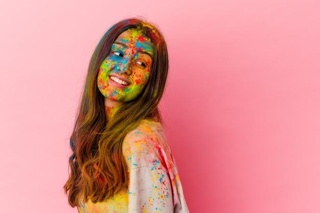白い壁に隔離された聖なる祭りを祝う若い女性は、笑顔、陽気で楽しい脇に見えます