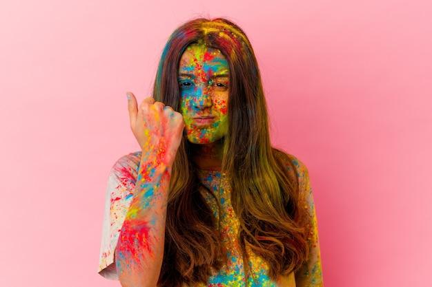 カメラに拳、攻撃的な表情を示す白い壁に分離された聖なる祭りを祝う若い女性