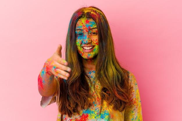 挨拶ジェスチャーでカメラで手を伸ばす白い壁に分離された聖なる祭りを祝う若い女性