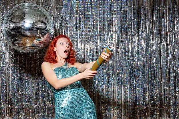 Giovane donna che celebra il nuovo anno che soffia petardo in festa su tende luminose