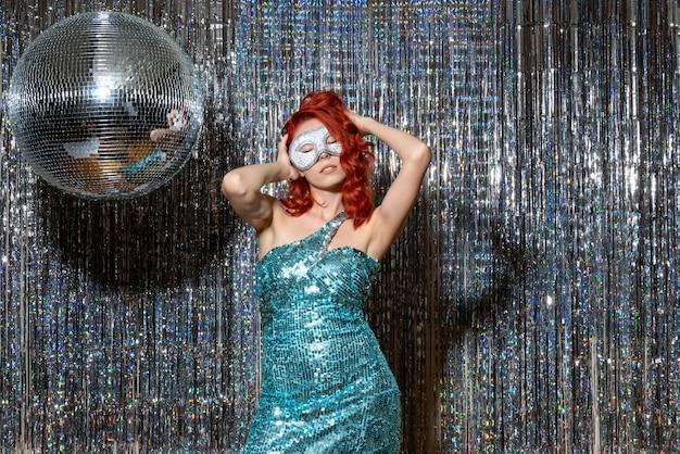 明るいカーテンでパーティーでマスクで新年を祝う若い女性